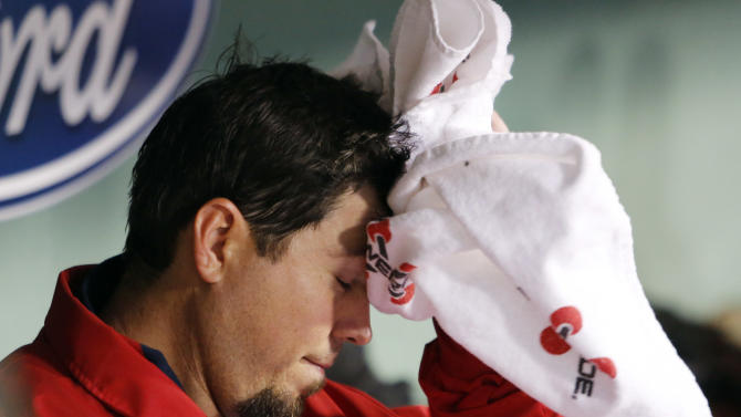 Boston Red Sox starting pitcher Josh Beckett wipes his head in the dugout after being taken out in the third inning of a baseball game against the Cleveland Indians in Boston, Thursday, May 10, 2012. (AP Photo/Michael Dwyer