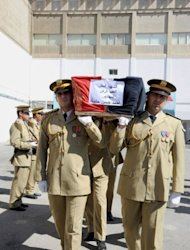 A handout picture provided by the Syrian Arab News Agency (SANA) shows Syrian security forces carrying the coffin of a comrade, Colonel engineer Ahmed Hasan Halbiah, who the agency said was killed in recent unrest in the country, during a funeral outside the Tishrin military hospital in Damascus