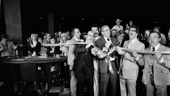FILE - In this May 26, 1978 file photo, New Jersey's Gov. Brendan Byrne cuts ribbon opening the east's first gambling casino in Atlantic City. He is surrounded by legislators that voted for the gambling legislation. At the beginning of 2007, Atlantic City's 11 casinos were at the top of a wave of prosperity. Starting with the 1978 opening of Resorts, America's first casino outside Nevada, Atlantic City for years was the only place to play slots, cards, dice or roulette in the eastern half of the United States. The cash kept pouring in, the busloads of visitors kept coming and the revenue charts went one way: straight up. And then, they didn't. Now, battered by competition from casinos all around it, Atlantic City is in a fight for its very survival. (AP Photo, File)