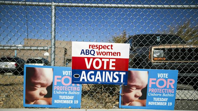 Signs advocating for and against a late term abortion ban hang on a fence outside of a voting site at Eisenhower Middle School in Albuquerque, N.M., Tuesday, Nov. 19, 2013. Albuquerque voters will decide whether to ban abortions after 20 weeks following an emotional and graphic campaign that has included protests and hundreds of thousands of dollars on television and radio ads that have brought out more than twice as many early voters as the recent mayoral elections. (AP Photo/Juan Antonio Labreche)