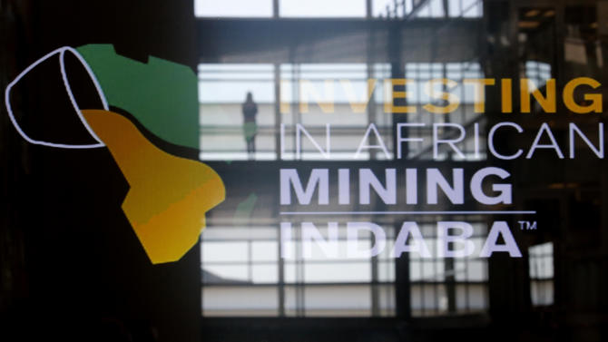 Delegates walk under a sign at the Investing in African Mining Inbaba in Cape Town