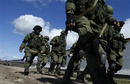 Armed men, believed to be Russians, march at the Ukrainian military base in Perevalnoye