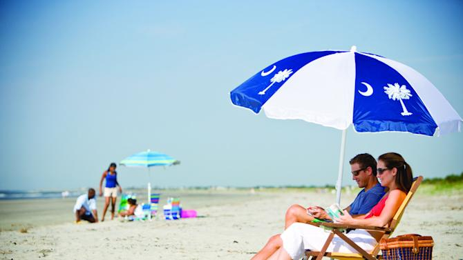 """FILE-  In this file photo provided the Charleston Area Convention & Visitors Bureau, people sit on a beach in Kiawah Island, S.C. Nearby Beachwalker Park on Kiawah Island is ninth on the 2012 list of Top 10 Beaches produced annually by coastal expert Stephen P. Leatherman, also known as """"Dr. Beach,"""" director of Florida International University's Laboratory for Coastal Research. (AP Photo/Charleston Area Convention & Visitors Bureau, File)"""