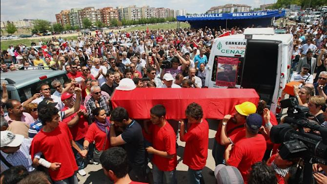 People carry the coffin of Ethem Sarisuluk, one of five people killed during the recent protests in Turkey, as Turkish riot police spray water cannon at demonstrators who remained defiant after authorities evicted activists from an Istanbul park, making clear they are taking a hardline against attempts to rekindle protests that have shaken the country, in city's main Kizilay Square in Ankara, Turkey, Sunday, June 16, 2013.(AP Photo )