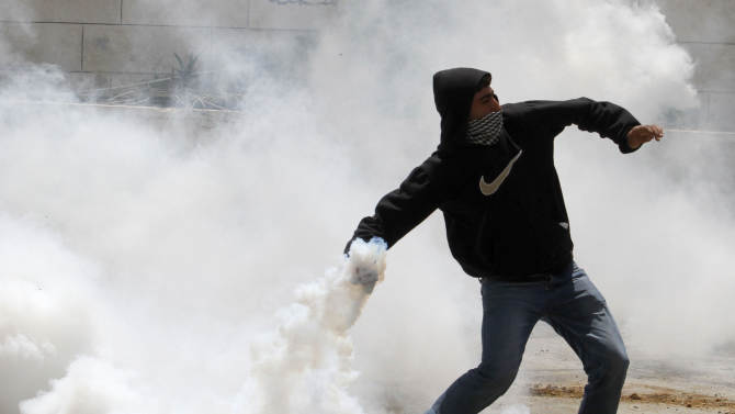 """A masked Palestinian throws back a tear gas canister during clashes after a rally marking the Nakba Day outside the West Bank town of Hebron, Wednesday , May 15, 2013. Palestinians annually mark the """"nakba,"""" or """"catastrophe"""" the term they use to describe their defeat and displacement in the war that followed Israel's founding in 1948. (AP Photo/Nasser Shiyoukhi)"""
