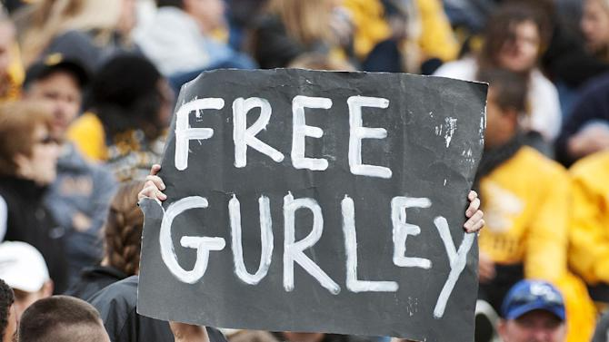 In this Oct. 11, 2014, file photo, a Georgia fan holds a sign in support of Georgia running back Todd Gurley who was suspended earlier this week, during the second quarter of an NCAA college football game against Missouri in Columbia, Mo. Georgia will file a request with the NCAA for Gurley's eligibility to be reinstated. Gurley has been suspended for the last two games while Georgia investigated allegations he broke NCAA rules by receiving improper benefits