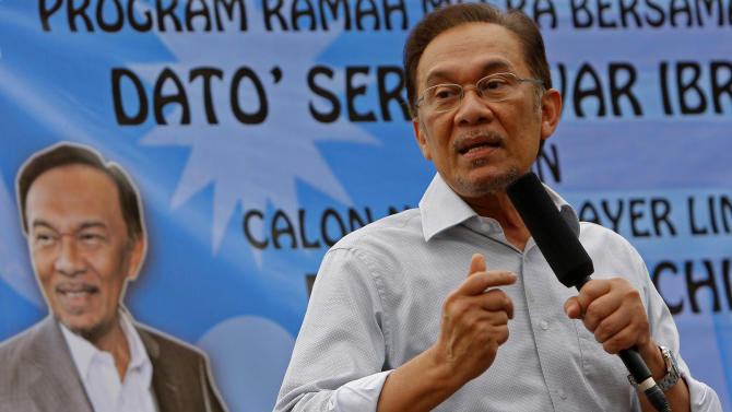 In this Tuesday, April 23, 2013 photo, Malaysian opposition leader Anwar Ibrahim speaks during an election campaign rally in Lubok China, Melaka state, Malaysia. With less than a week to general elections, Malaysia's opposition alliance is banking on the promise of bold change to end the governing coalition's 56-year rule. It says a new economic playing field will strip away decades of race-based policies that it believes bred corruption and hampered growth. (AP Photo/Lai Seng Sin)