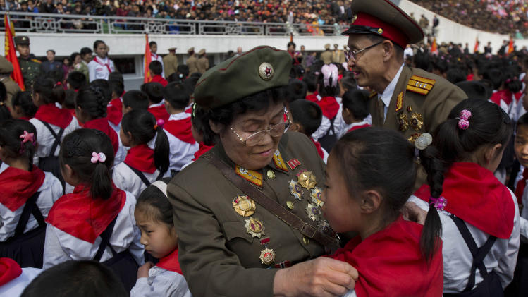 Retired North Korean military members tie red bandanas around the necks of children during an induction ceremony into the Korean Children's Union, the first political organization for North Koreans, held at a stadium in Pyongyang on Friday, April 12, 2013. (AP Photo/David Guttenfelder)
