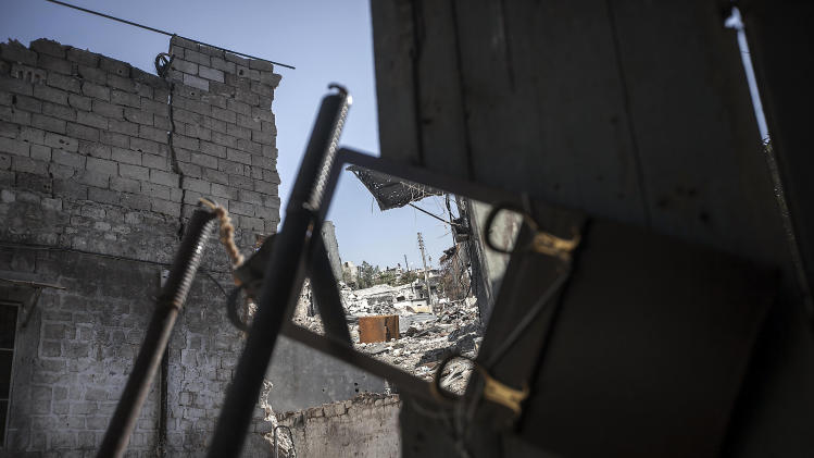 In this Tuesday, Nov. 13, 2012 photo, a street of destroyed buildings is reflected in a mirror used by rebel fighters to keep an eye on a Syrian army position in Aleppo, Syria. (AP Photo/Narciso Contreras)