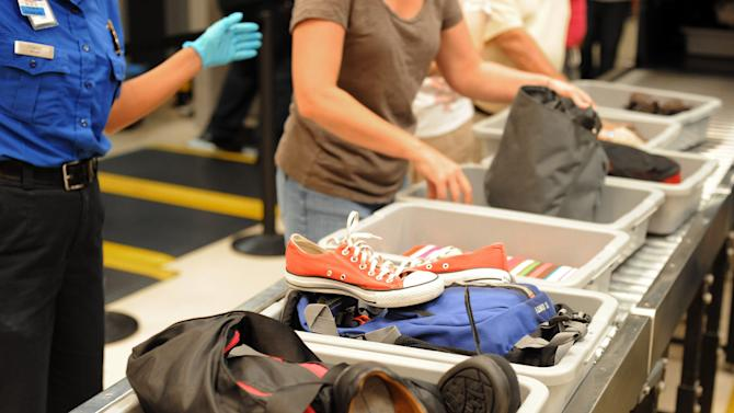"""FILE - In this Aug. 3, 2011, file photo, airline passengers retrieve their scanned belongings while going through the Transportation Security Administration security checkpoint at Hartsfield-Jackson Atlanta International Airport, in Atlanta. Airline executives said Tuesday, Oct. 16, 2012, at a global aviation conference that Airport security needs to undergo a radical overhaul or else passengers will become further disgruntled, lines will grow and terminals will be overwhelmed. """"We simply can't cope with the expected volume of passengers with the way things are today,"""" said Tony Tyler, director general and CEO of the International Air Transport Association, the airlines' trade group. (AP Photo/Erik S. Lesser, File)"""