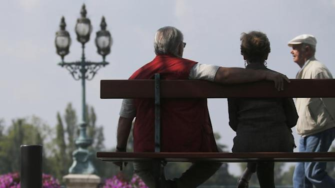 A retired couple sits on a bench in Enghien-les-Bains