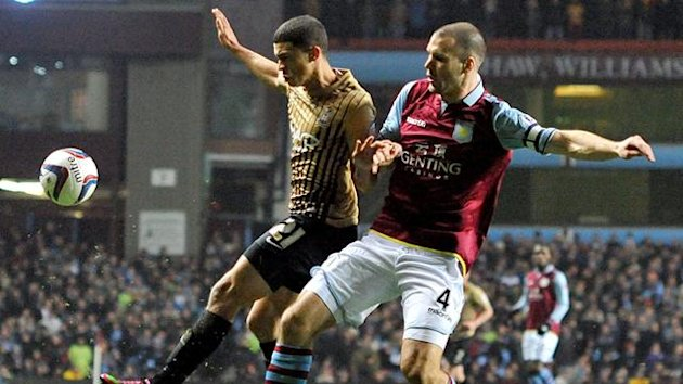 Aston Villa's Ron Vlaar (right) and Bradford City's Nahki Wells (left) battle for the ball (PA Photos)