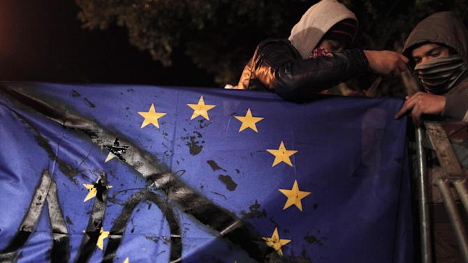 "Protesters hold an EU flag during a protest outside the Cypriot parliament, Friday, March 22, 2013. Cypriot authorities were putting the final touches Friday to a plan they hope will convince international lenders to provide the money the country urgently needs to avoid bankruptcy within days. ""The next few hours will determine the future of this country,"" said government spokesman Christos Stylianides.(AP Photo/Petros Giannakouris)"