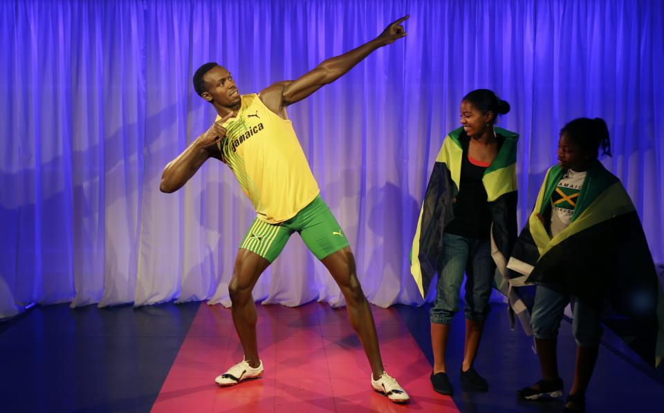 In this Monday, July 23, 2012 photo, fans look at the new wax model of Jamaican sprinter Usain Bolt, at a photocall for its launch at the Madame Tussauds wax museum, ahead of the 2012 Summer Olympics, in London. (AP Photo/Ben Curtis)