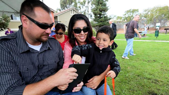 Evan Houston helps his Mom, Maria and Dad Staff Sgt Matthew Houston open a new Kindle during a Kindle giveaway for wounded sevice members in Oceanside, CA on Thursday, November 8, 2012.  Amazon is donating over 2,000 Kindles to wounded service members ahead of Veterans Day and is committing to hire 1,200 Veterans in the upcoming year. (Sandy Huffaker /AP Images for Amazon)