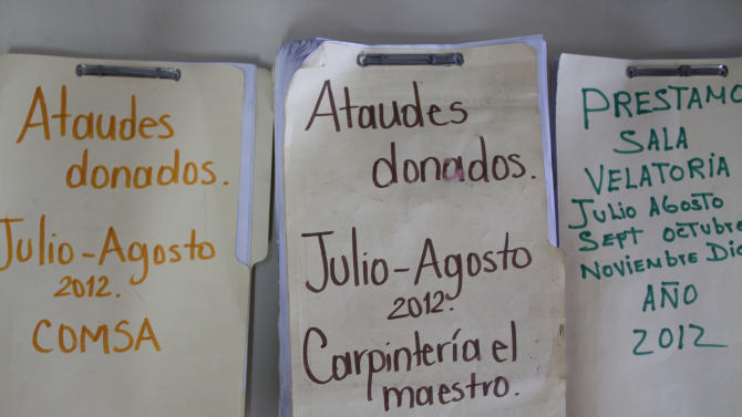 In this Aug. 17, 2012 photo, folders with information on donated coffins and loan wake rooms sit in the office at the Funeraria del Pueblo, or People's Mortuary, in Tegucigalpa, Honduras. The charities that provide the coffins, and sometimes free transportation and soft drinks to the bereaved, are run using public funds by three elected officials, two of whom are seeking the presidency and a third who is running for mayor of Tegucigalpa. The charities say the coffins are not a pitch for votes, but an important service to constituents who cannot afford a coffin.  (AP Photo/Esteban Felix)