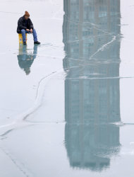 Despite unseasonably warm temperatures, Don Skaiicki ice fishes in Chicago's Belmont Harbor along Lake Michigan Tuesday, Jan. 29, 2013, in Chicago. Unseasonably warm temperatures broke records in the Chicago area with thunderstorm expected to usher in freezing temperatures and snow Wednesday. (AP Photo/Charles Rex Arbogast)
