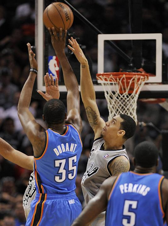 San Antonio Spurs guard Danny Green, center, defends Oklahoma City Thunder forward Kevin Durant, left, during the first half of an NBA basketball game, Saturday, Dec. 21, 2013, in San Antonio