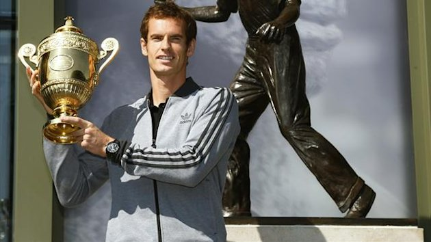 Tennis player Andy Murray of Britain holds the trophy under a statue of former British champion Fred Perry, at Wimbledon, southwest London July 8, 2013. (Reuters)