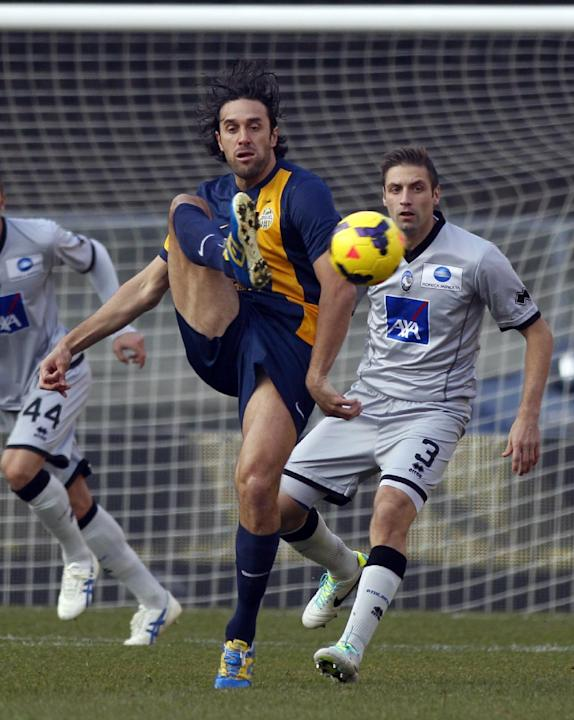 Hellas Verona's Luca Toni, left, is chased by Atalanta's Stefano Lucchini during a Serie A soccer match at Bentegodi stadium in Verona, Italy, Sunday, Dec. 8, 2013