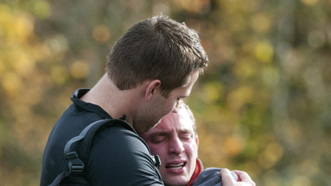 Jim Hanchett, LDS youth leader hugs Jackson Chandler, one of two Oregon teenagers who didn't return from a weekend hike, Monday, Oct. 29, 2012, in Portland, Ore. The teens were found Monday afternoon by a driver not connected to the search party, safe after spending two nights in wet, windy weather. (AP Photo/The Oregonian, Brent Wojahn)  MAGS OUT; TV OUT; LOCAL TV OUT; LOCAL INTERNET OUT; THE MERCURY OUT; WILLAMETTE WEEK OUT; PAMPLIN MEDIA GROUP OUT