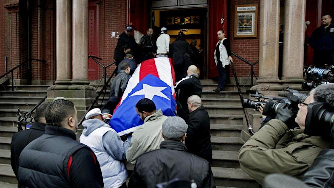 """Hector """"Macho"""" Camacho's casket is brought up the steps of St. Cecilia's Roman Catholic Church in New York for a funeral, Saturday, Dec. 1, 2012. Doctors pronounced Camacho dead on Saturday, Nov. 24, after he was removed from life support at his family's direction. He never regained consciousness after at least one gunman crept up to his car in a darkened parking lot in Puerto Rico and opened fire. (AP Photo/Richard Drew)"""