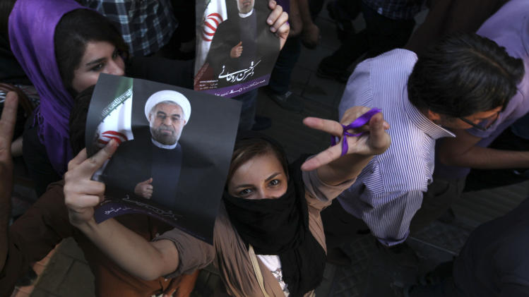 A female supporter of Iranian presidential candidate Hasan Rowhani, flashes a victory sign as she holds his poster during a celebration gathering in Tehran, Iran, Saturday, June 15, 2013. Moderate cleric Hasan Rowhani was declared the winner of Iran's presidential vote on Saturday after gaining support among many reform-minded Iranians looking to claw back a bit of ground after years of crackdowns. (AP Photo/Vahid Salemi)