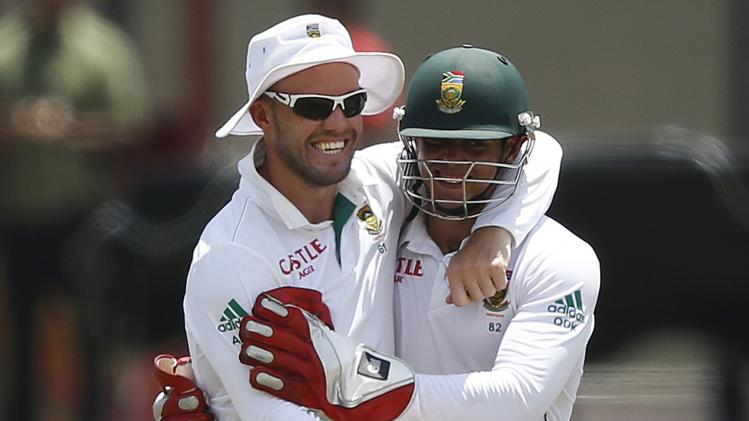 South Africa's de Villiers celebrates with teammate de Kock after taking a catch to dismiss Sri Lanka's Silva during the first day of their second test cricket match in Colombo