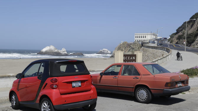 In this photo taken Tuesday, May 14, 2013 a pair of cars park for free by Ocean Beach and the Cliff House in San Francisco. For the right to frolic in the sand, sunbathers to Southern California beaches are used to feeding the meter or paying a parking attendant.Not so along the less developed north coast where it's customary to ditch cars on the shoulder of Highway 1 to surf, swim or picnic. That sandy line that long defined California's disparate beach culture may soon fade. In search of new revenue, the state parks system is eyeing parking fees for parts of the Northern California shoreline where none existed or hiking rates to visit popular beaches south of Los Angeles during peak periods. (AP Photo/Eric Risberg)