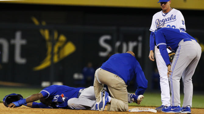 A trainer works on Toronto Blue Jays' Jose Reyes after he injured his leg while stealing second base during the sixth inning of a baseball game against the Kansas City Royals at Kauffman Stadium in Kansas City, Mo., Friday, April 12, 2013. Blue Jays second baseman Emilio Bonifacio (1) and Royals second baseman Elliot Johnson (23) stand to the side. (AP Photo/Orlin Wagner)