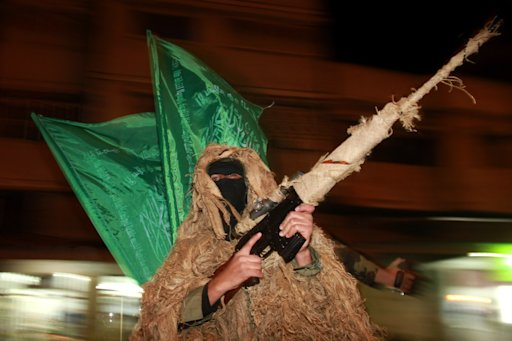 A masked Hamas militant covered in camouflage material holds up his gun during a parade to mark the third anniversary of the Israeli offensive on Gaza in 2008, in Gaza City, Tuesday, Dec. 27, 2011. Palestinians mark the third anniversary of the three-week offensive Israel launched in Gaza in late 2008.  (AP Photo/Hatem Moussa)