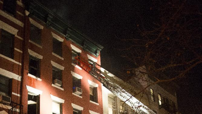 Firefighters respond to a five-alarm fire at a lower Manhattan apartment building that killed one woman in New York Thursday, Jan. 10, 2013, in New York. (AP Photo/John Minchillo)