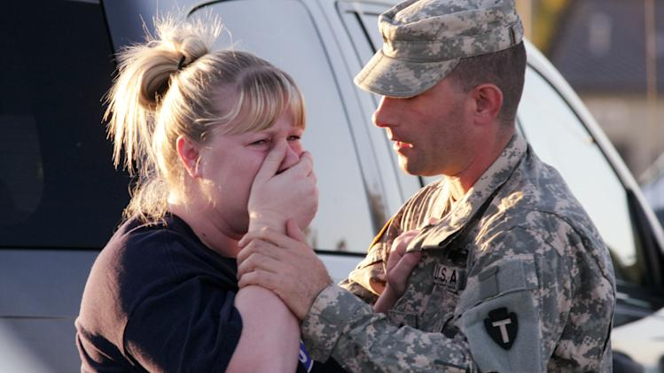 FILE- In this Nov. 5, 2009, file photo, Sgt. Anthony Sills, right, comforts his wife as they wait outside the Fort Hood, Texas, army base where their young son was in daycare. Nidal Hasan is charged in the 2009 shooting rampage at Fort Hood that left 13 dead and more than 30 others wounded. Hasan doesn't deny that he carried out the rampage, but military law prohibits him from entering a guilty plea because authorities are seeking the death penalty. If he is convicted and sentenced to death in a trial that starts Tuesday, Aug. 6, 2013, there are likely years, if not decades, of appeals ahead. (AP Photo/Jack Plunkett, File)