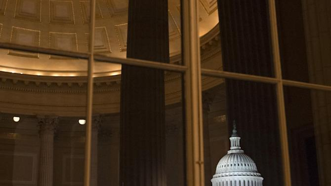 The U.S. Capitol is seen amid reflections from inside the Cannon House Office Building on the last day of the 112th Congress, on Capitol Hill in Washington, Wednesday, Jan. 2, 2013. On Thursday, all members of the House of Representatives and one third of the Senate will be sworn in as the 113th Congress begins its work. (AP Photo/J. Scott Applewhite)