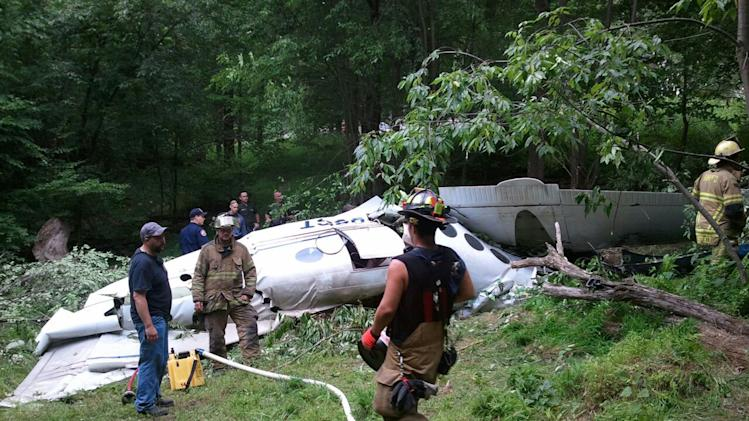 In this photo provided by Mike Nichols of Aphelion Aviation, emergency personnel work the scene of a small plane crash in Coopers Rock State Forest, 7.5 miles east of Morgantown, W.Va. on Friday, June 22. 2012. Monongalia County Sheriff Al Kisner confirmed one person was killed when the Hawker Beechcraft BE90 struck a radio tower and crashed. (AP Photo/Mike Nichols) MANDATORY CREDIT