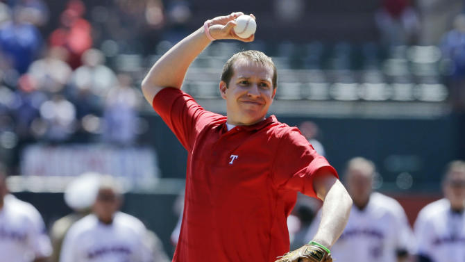 Robbie Parker throws out the ceremonial first pitch before a baseball game between the Los Angeles Angels and Texas Rangers Friday April 5, 2013, in Arlington, Texas. Parker, a North Texas native whose 6-year-old daughter, Emilie, was among the victims of the Sandy Hook school shooting in Connecticut, threw out the first pitch before the Rangers' home-opener, their favorite team. (AP Photo/Tony Gutierrez)