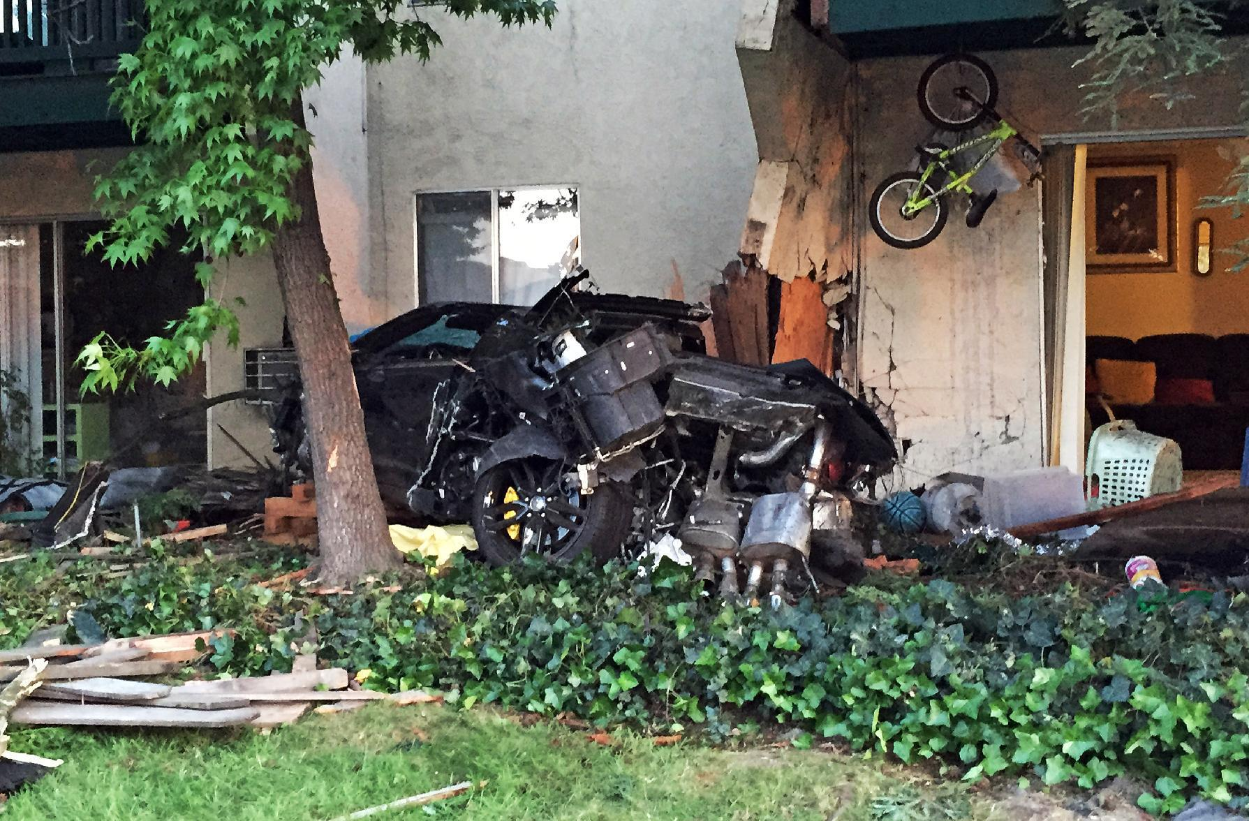 Car smashes into complex, kills woman, child walking outside