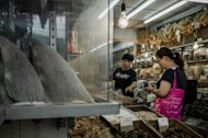 A customer (R) talks to a shopkeeper in a store selling shark fins (L) in Hong Kong on September 5, 2012