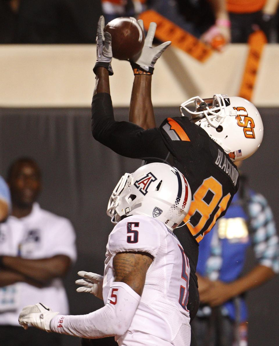 Oklahoma State wide receiver Justin Blackmon, rear, reaches for a pass for a touchdown in front of Arizona defender cornerback Shaquille Richardson, front, in the third quarter of an NCAA college football game in Stillwater, Okla., Thursday, Sept. 8, 2011. (AP Photo/Sue Ogrocki)