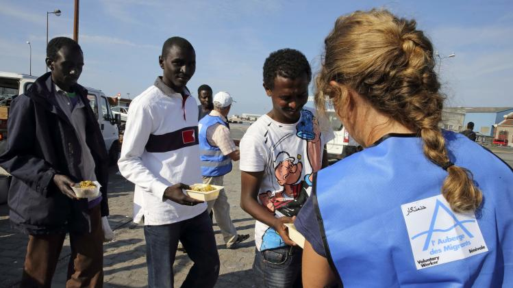 "A volunteer from ""Auberge des Migrants"" gives soup to a migrant during a daily food distribution in Calais"