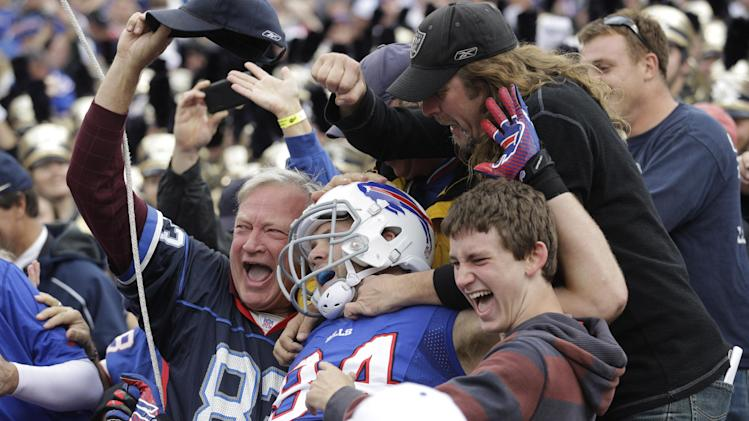 Buffalo Bills' Scott Chandler (84) celebrates his touchdown catch with fans against the New England Patriots during the first half of an NFL football game in Orchard Park, N.Y., Sunday, Sept. 30, 2012. (AP Photo/Gary Wiepert)