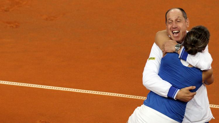 Italy's team captain Corrado Barazzutti, top, hugs Sara Errani at the end of a Fed Cup World group tennis double match against United States' Varvara Lepchenko and Liezel Huber at the 105 stadium in Rimini, Italy, Sunday, Feb. 10, 2013. Errani and Vinci won 6-2, 6-2. (AP Photo/Felice Calabro')