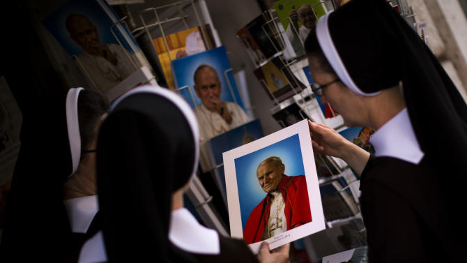 Poland nuns buy portraits of late Pope Pope John Paul II, in a shop near St. Peter's Square at the Vatican, Friday, April 25, 2014. Hundred thousands of pilgrims and faithful are expected to reach Rome to attend the scheduled April 27 ceremony at the Vatican in which Pope Francis will elevate in a solemn ceremony John XXIII and John Paul II to sainthood. (AP Photo/Emilio Morenatti)