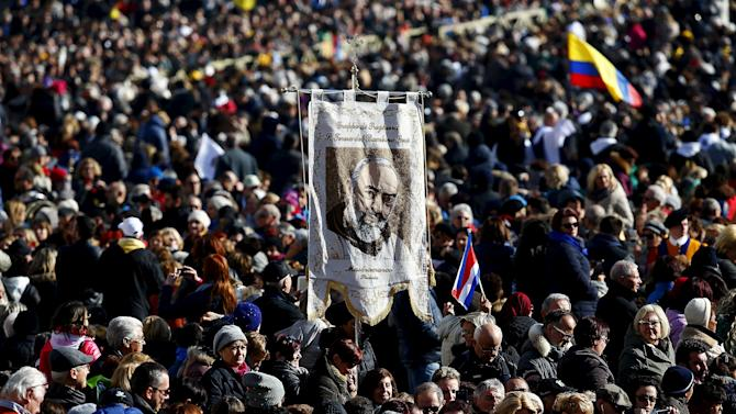 A faithful holds a banner as Pope Francis arrives to lead a special audience to celebrate a jubilee day for the mystic saint Padre Pio in Saint Peter's square at the Vatican