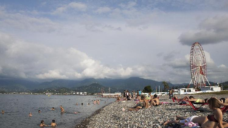 In this Aug. 1, 2012, photo, tourists swim and sunbathe in the Black Sea resort town of Batumi in Georgia. The transformation of Batumi, an ancient city of 180,000 near the border with Turkey, is a vivid example of Georgia's drive to capitalize on its tourism potential in a bid to boost the economy in this struggling ex-Soviet nation, where nearly 1/5 of the population lives in poverty, according to conservative estimates. The government has attracted top foreign investors, such as U.S. estate magnate Donald Trump, to build hotels and develop and renovate tourist sites and aggressively marketed Georgia as tourism hot spot abroad. (AP Photo/Maria Danilova)