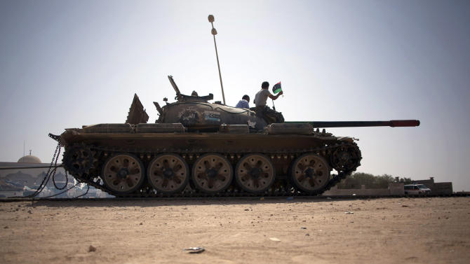 Civilians celebrate atop a revolutionary forces tank near Sirte, Libya, Sunday, Sept. 25, 2011. Gunmen loyal to Moammar Gadhafi have crossed the Libyan border from Algeria and attacked revolutionary forces in a town near the frontier, killing six people, officials said Sunday. (AP Photo/Manu Brabo)