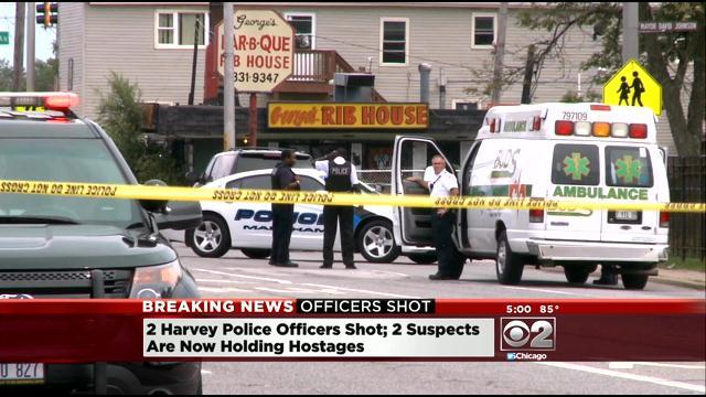Two Harvey Cops Shot; Offenders Take Six Hostage
