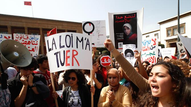 "FILE - In this March 17, 2012 file photo, women hold posters as they protest in support of Amina Filali who committed suicide in March 2012 in front the Moroccan parliament in Rabat, Morocco. Amina Filali took her own life by taking rat poison after being forced to marry the man who allegedly raped her at age 15, and then abused her in marriage. A new poll of 50,000 people across 34 African countries finds attitudes toward women's equality are dimmest in the predominantly Muslim north. The poll by Afrobarometer, conducted between 2011 and 2013, found women in general are at a disadvantage compared to men, but support for women's equality is growing more widespread. Placard reads ""Law killed me"". (AP Photo/Abdeljalil Bounhar)"
