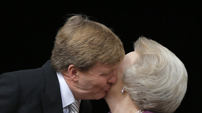Dutch King Willem-Alexander kisses his mother Princess Beatrix on the balcony of the Royal Palace in Amsterdam, The Netherlands, Tuesday April 30, 2013. Around a million people are expected to descend on the Dutch capital for a huge street party to celebrate the first new Dutch monarch in 33 years. (AP Photo/Daniel Ochoa de Olza)