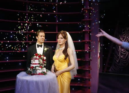 Wax models of actors Brad Pitt and Angelina Jolie have confetti thrown on them after being presented with a wedding cake and a bridal veil to celebrate their recent wedding, at the Madame Tussauds attraction in Sydney